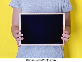 woman holding blank black chalkboard