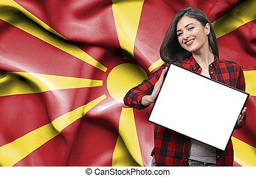 Woman holding blank board against national flag of Macedonia