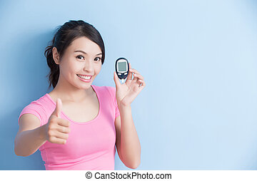 Woman holding a blood glucose meter to prevention diabetes isolated on blue background, asian