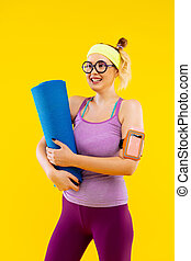 Woman holding blue sport mat feeling excited and energized