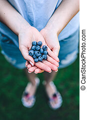 Woman holding blueberries in her hands