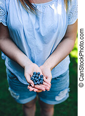 Woman holding blueberry fruits in her hands