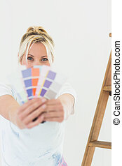 Woman holding blurred color swatches in new house