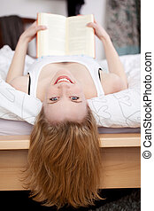 Woman Holding Book While Lying In Bed
