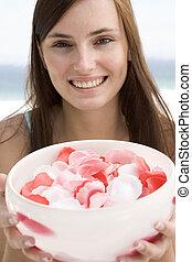 Woman holding bowl of petals