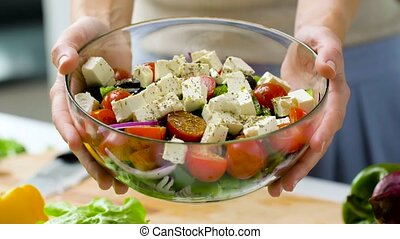 woman holding bowl of vegetable salad with feta - healthy ...