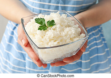 Woman holding bowl with delicious rice, close up