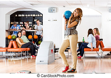 Woman Holding Bowling Ball in Club