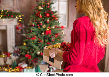 Woman holding box with baubles