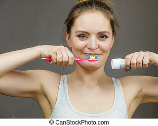 Woman holding brush and tooth paste