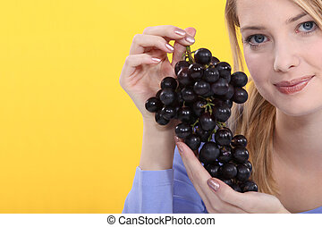 Woman holding bunch of grapes