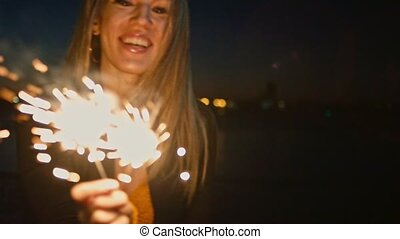 Woman holding burning sparkler. Cheerful young woman holding...