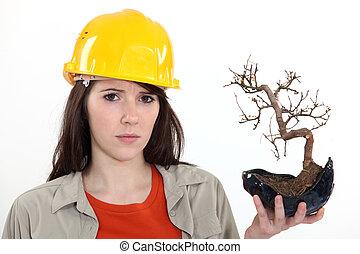 Woman holding burnt tree