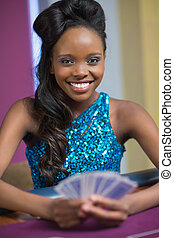 Woman holding cards while smiling at casino