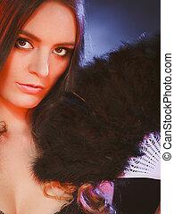 Woman holding carnival feather fan in hand.