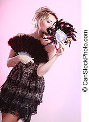 Woman holding carnival mask feather fan in hand