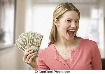 Woman Holding Cash - A young woman is holding up cash in a...