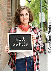 "Woman holding chalkboard with text ""bad habits""."
