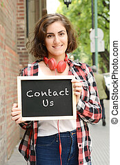 "Woman holding chalkboard with text ""contact us""."