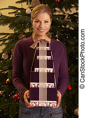 Woman Holding Christmas Gifts In Front Of Tree