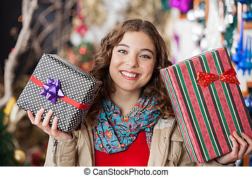 Woman Holding Christmas Presents In Store