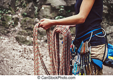 Woman holding climbing rope near the rock - Climber woman...