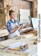 Woman Holding Clipboard in Woodworks Shop - Portrait of...