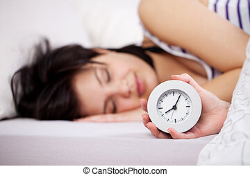 Woman Holding Clock While Sleeping In Bed