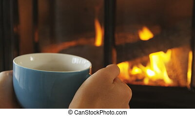 Woman Holding Coffee Cup By Fireplace In Winter In Slow ...