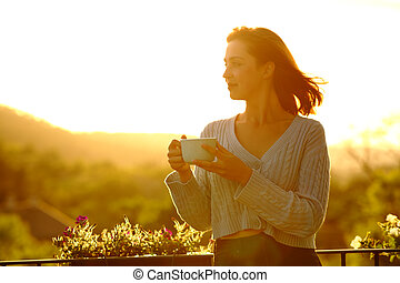 Woman holding coffee cup contemplating at sunset in a balcony