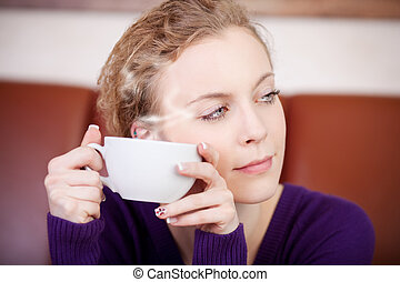 Woman Holding Coffee Cup While Looking Away In Cafe