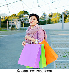 woman holding colored paper shopping bags