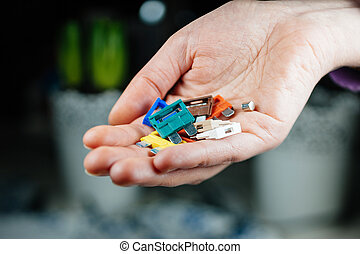 Woman holding colorful amp car fuses defocused background