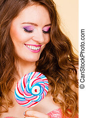 Woman holding colorful lollipop candy in hand.