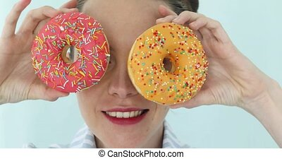 Woman holding colorful pink donuts against her eyes