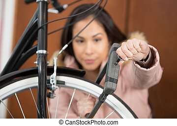woman holding combination bike lock in front of bicycle