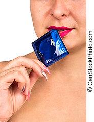 Woman holding condom in teeth