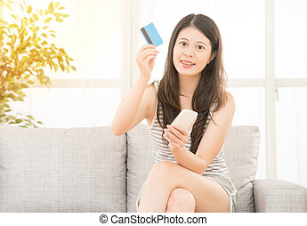 woman holding credit card phone for shopping
