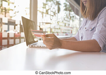 woman holding credit card with laptop computer for online shopping
