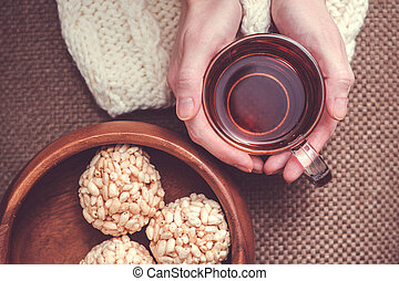 Woman holding cup of black tea