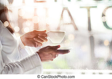 Woman holding cup of coffee in a cafe on raindrop background. Drinking. Coffee lover.
