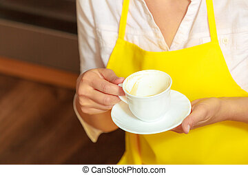 Woman holding cup of coffee in kitchen.
