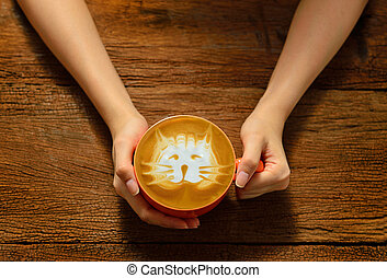 Woman holding cup of coffee latte