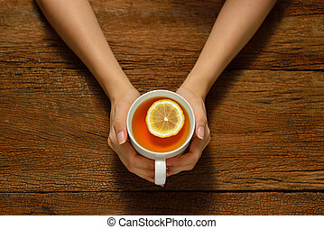 Woman holding cup of tea with lemon on wooden table
