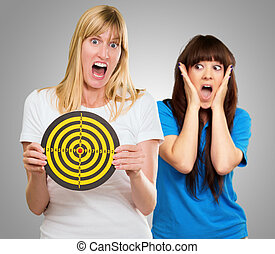 Woman Holding Dartboard In Front Of Shocked Woman
