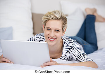 Woman Holding Digital Tablet While Lying On Bed