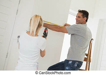 Woman holding drill while man measuring wall