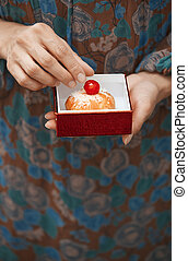 Woman holding eclair in the box