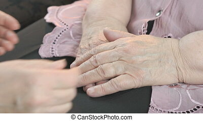 Woman holding flabby wrinkled hands of old woman