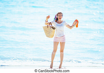 woman holding flip flops and listening to music with headphone